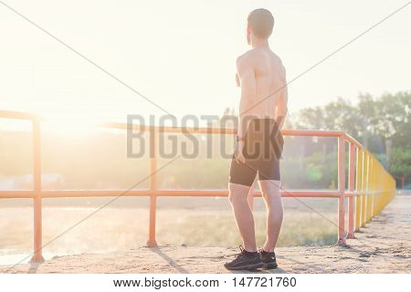 Young athlete man is looking out at sunset