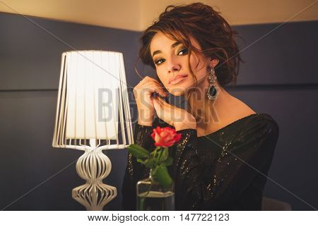 Young cute brunette lady with curly hair sitting in cafe at table with vase of fresh white rose flower waiting looking forward horizontal picture