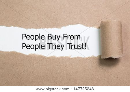 Motivational quote People Buy From People They Trust, appearing behind torn paper