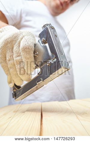 Male installer using stapler for wooden plank