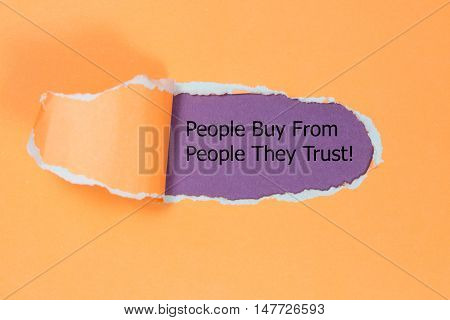 Motivational quote People Buy From People They Trust, appearing behind paper.