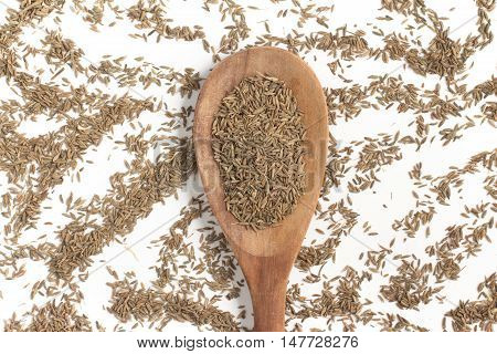 Cumin seeds into a spoon isolated in white background