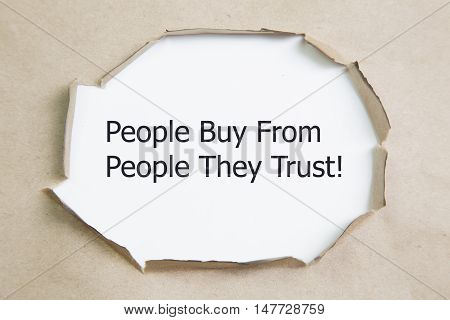 Motivational quote People Buy From People They Trust, appearing behind torn paper.