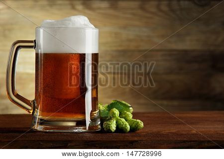 mug of beer and hops..on a wooden table