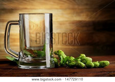 empty mug and hops.on a wooden table