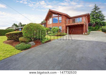Luxury House Exterior With Wooden Pannel Trim, Garage And Well Kept Garden Around.