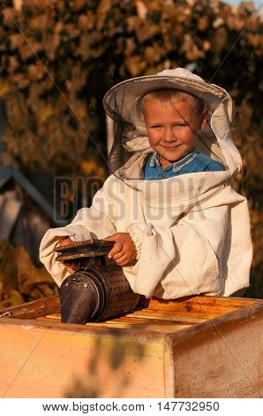 beekeeper portrait of a young boy who works in the apiary at hive with smoker for bees in hand.