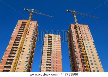 High-rise buildings under construction, construction cranes, sky