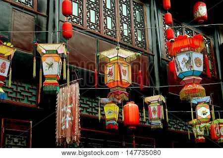 Chengdu China: April 12 2006: Colourful Chinese lanterns hang from wires in front of traditional wooden buildings with lattice-work windows on Jin Li Street