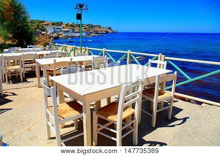 Beautiful outdor cafe with white tabes and chairs on Mediterranean sea coast, Crete island, Greece.