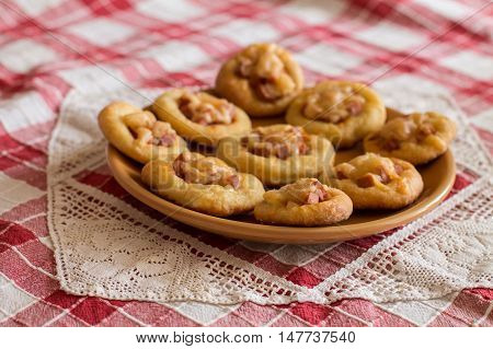 Mini pizzas with sausage and cheese in orange plate on checkered tablecloth.