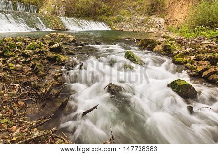 Gradac river with the waterfalls in background,. Long exposure of white water rapids and waves along section of the Gradac river, Serbia