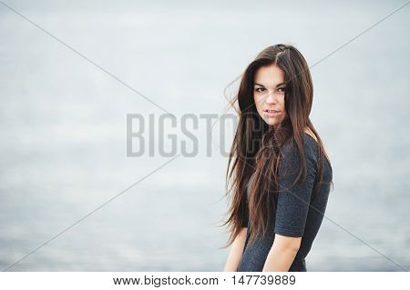 Portrait of beautiful brown-eyed girl with long tangled from the wind hair in a dark shirt on grey-blue background