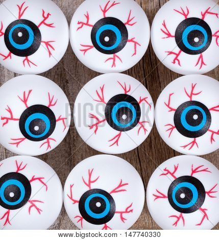 Scary eyeballs for Halloween season on rustic wooden boards.