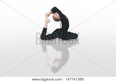 beautiful girl in a black suit doing yoga on white background