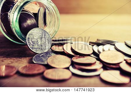 Save money concept, Coins spilling out of a glass bottle, Money for income and expenditure selective focus Save money for prepare vintage style