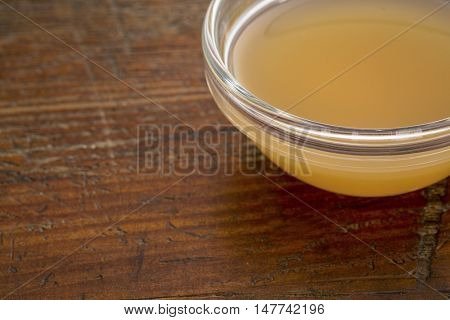unfiltered, raw apple cider vinegar with mother  - a small glass bowl against rustic wood with a copy space