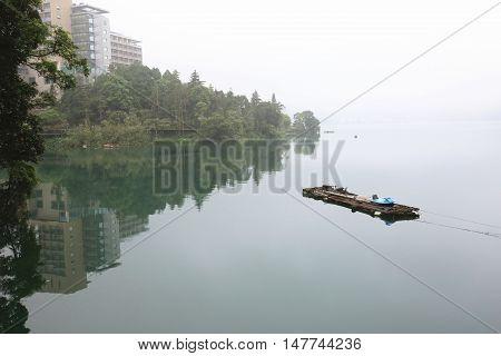 Peaceful lake scenery with a bamboo raft and reflection of trees and building in the foggy morning
