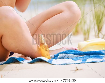 Skin protection in summer. Woman on beach using sun oil. Young beauty girl taking sunbath on sunny day. Holidays time.