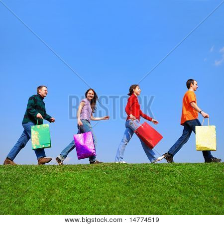 People with bags against blue sky