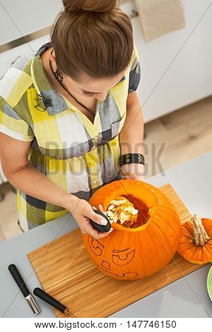 Woman In Halloween Decorated Kitchen Prepare Pumpkin For Carving