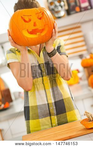 Woman Holding A Big Jack-o-lantern Pumpkin In Front Of Head