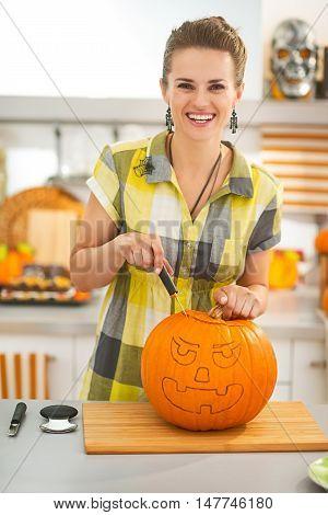 Woman In Kitchen Carving Big Orange Pumpkin Jack-o-lantern
