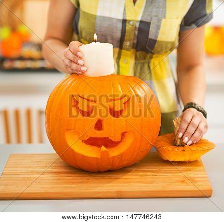 Closeup On Woman Putting Candle Inside Pumpkin Jack-o-lantern