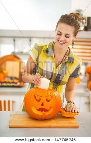 Housewife Putting Candle Inside Orange Pumpkin Jack-o-lantern