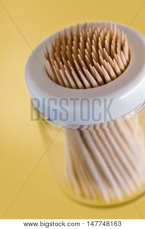 Closeup on many wooden toothpicks in a plastic container over yellow background