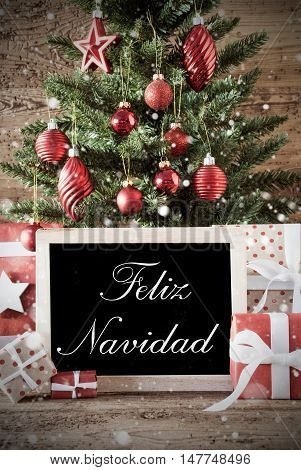 Nostalgic Christmas Card For Seasons Greetings. Christmas Tree With Balls. Gifts Or Presents In The Front Of Wooden Background. Chalkboard With Spanish Text Feliz Navidad Means Merry Christmas