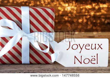 Macro Of Christmas Gift Or Present On Atmospheric Wooden Background. Card For Seasons Greetings Or Congratulations. White Ribbon With Bow. French Text Frohe Weihnachten Means Merry Christmas