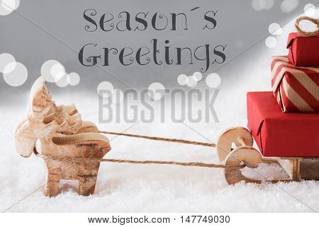 Moose Is Drawing A Sled With Red Gifts Or Presents In Snow. Christmas Card For Seasons Greetings. Silver Background With Bokeh Effect. English Text Seasons Greetings
