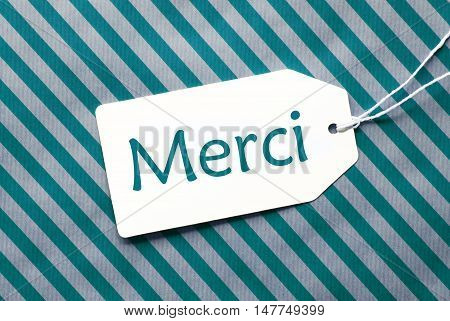 One Label On A Turquoise Striped Wrapping Paper. Textured Background. Tag With Ribbon. French Text Merci Means Thank You
