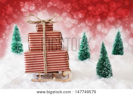 Sleigh With Christmas Gifts Or Presents. Snowy Scenery With Snow And Trees. Red Background With Bokeh Effect.
