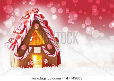 Gingerbread House In Snow As Christmas Decoration. Candlelight For Romantic Atmosphere. Red Background With Bokeh Effect. Copy Space For Advertisement