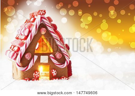 Gingerbread House In Snow As Christmas Decoration. Candlelight For Romantic Atmosphere. Bronze Or Golden Background With Bokeh Effect. Copy Space For Advertisement