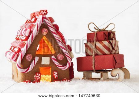 Gingerbread House In Snow As Christmas Decoration. Candlelight For Romantic Atmosphere. White Background. Sled With Gifts Or Presents