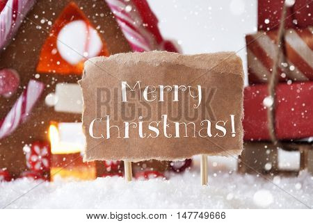 Gingerbread House In Snowy Scenery As Christmas Decoration. Sleigh With Christmas Gifts Or Presents And Snowflakes. Label With English Text Merry Christmas