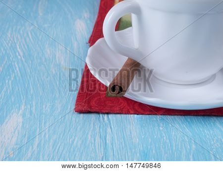 White Cup on a saucer with a cinnamon stick standing on a red napkin.
