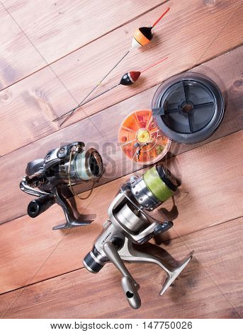 Fishing accessories reel spools of fishing line floats and a box of hooks on wooden background