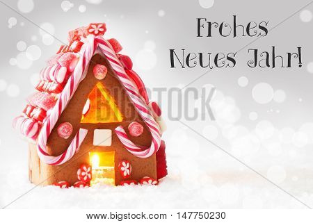 Gingerbread House In Snowy Scenery As Christmas Decoration. Candlelight For Romantic Atmosphere. Silver Background With Bokeh Effect. German Text Frohes Neues Jahr Means Happy New Year
