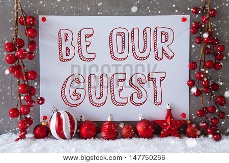 Label With English Text Be Our Guest. Red Christmas Decoration Like Balls On Snow. Urban And Modern Cement Wall As Background With Snowflakes.