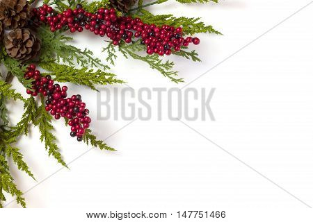 Christmas Garland with Pine Cones and Berries isolated on white with copy space or negative space for text or decoration