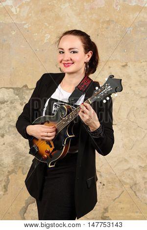 Beautiful smiling woman poses with black mini guitar in studio