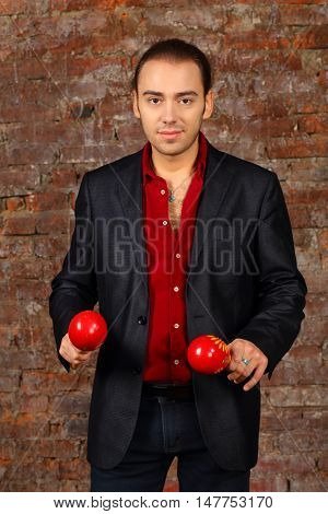 Young man in suit stands with red maracas in studio with brick wall