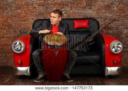 Handsome young man hits drums on sofa car with guitar in studio with brick wall