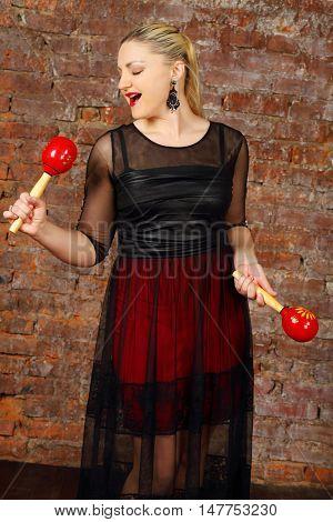 Pretty blonde woman in dress sings into maraca near red brick wall in studio