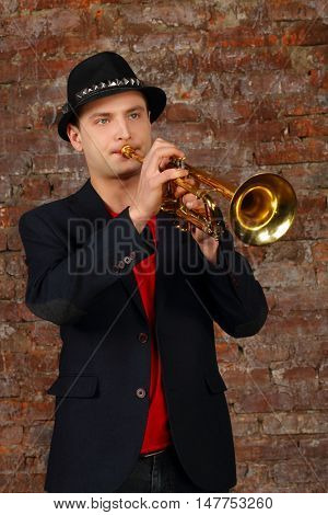 Young handsome man in suit and hat plays trumpet in studio with brick wall