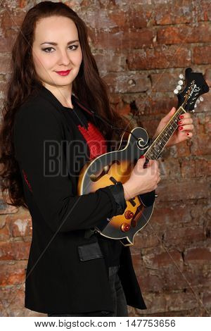 Pretty young woman hold mini guitar in studio with red brick wall